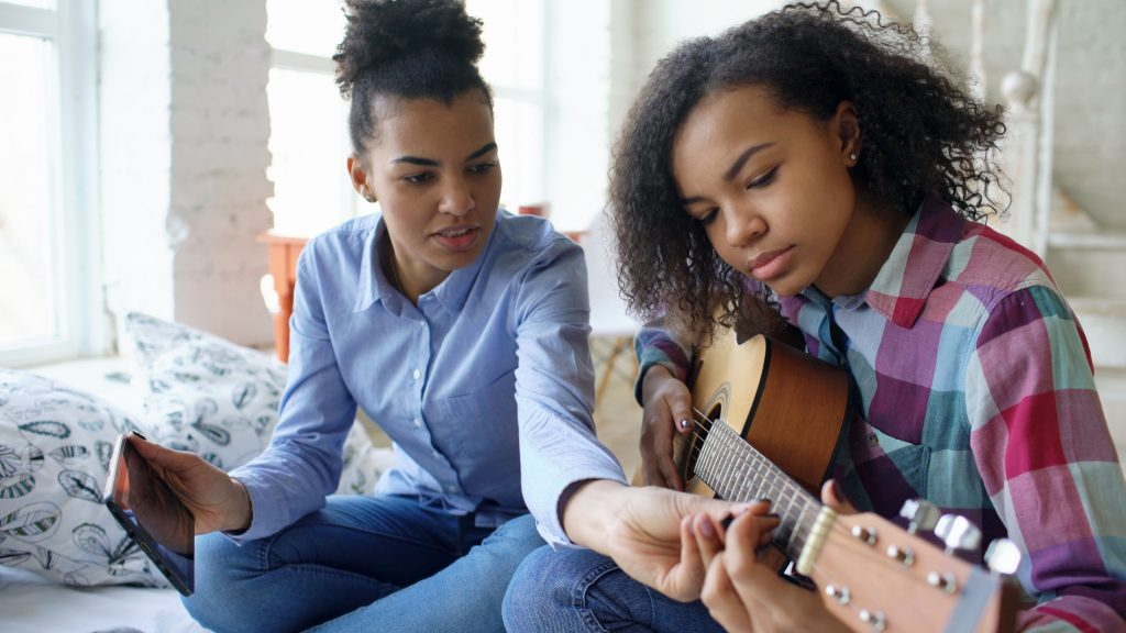A music teacher and her student during guitar lessons