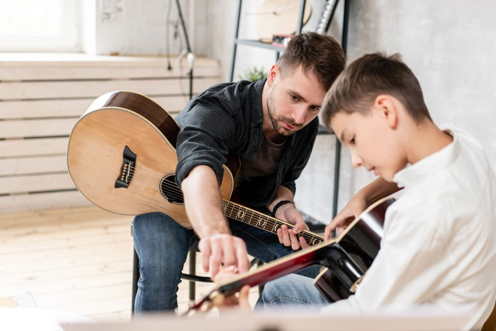 Music teacher and his student in their private guitar lessons