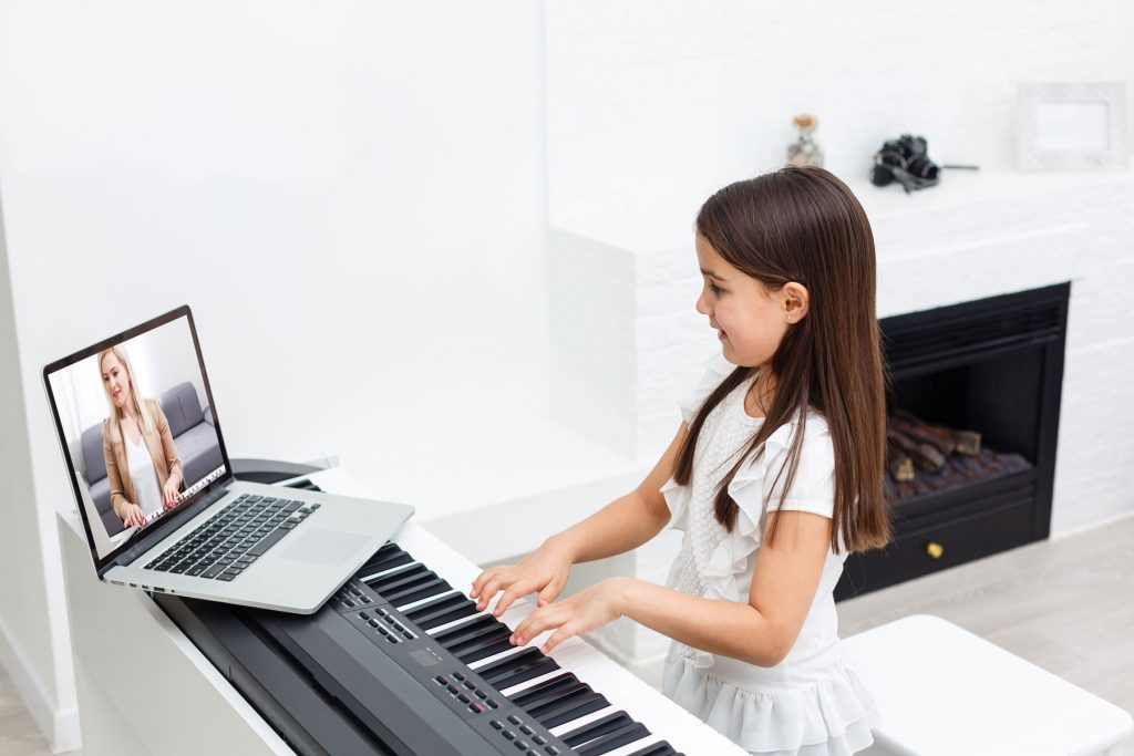 A beginner child learning how to play the piano via online