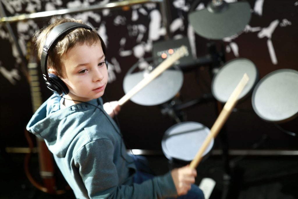 young boy wearing headphones is playing the drums
