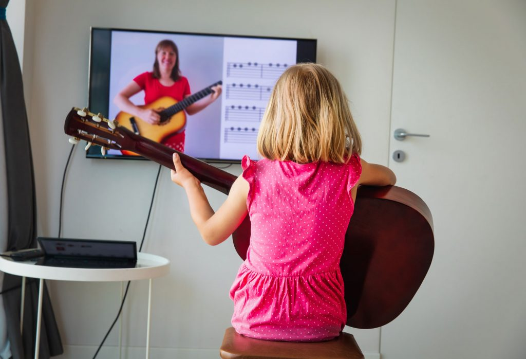 little girl playing guitar while watching her teacher play guitar on a big screen tv