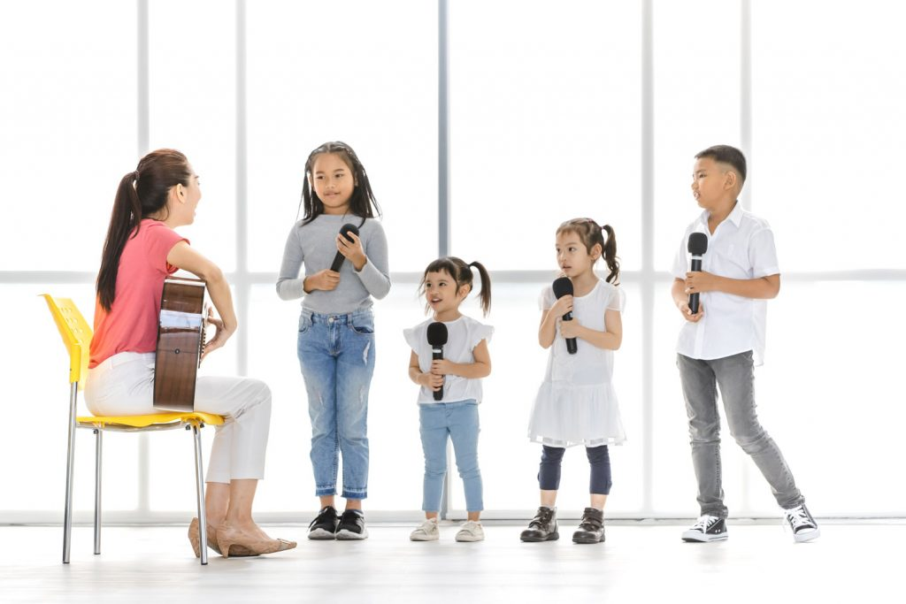 female music teacher playing guitar while teaching four young children to sing while they each hold a microphone