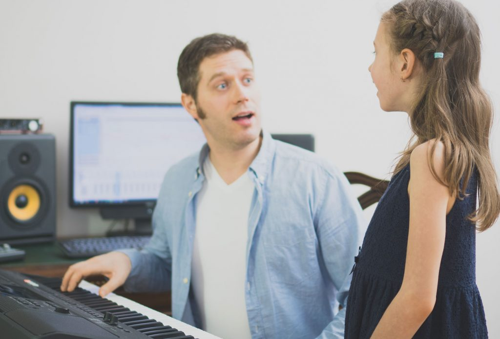 male vocal instructor teaching young girl to sing