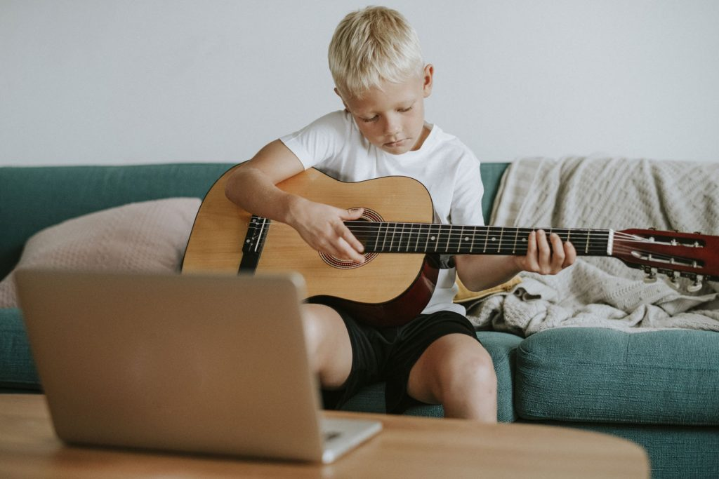 boy playing the guitar with the laptop open in front of him
