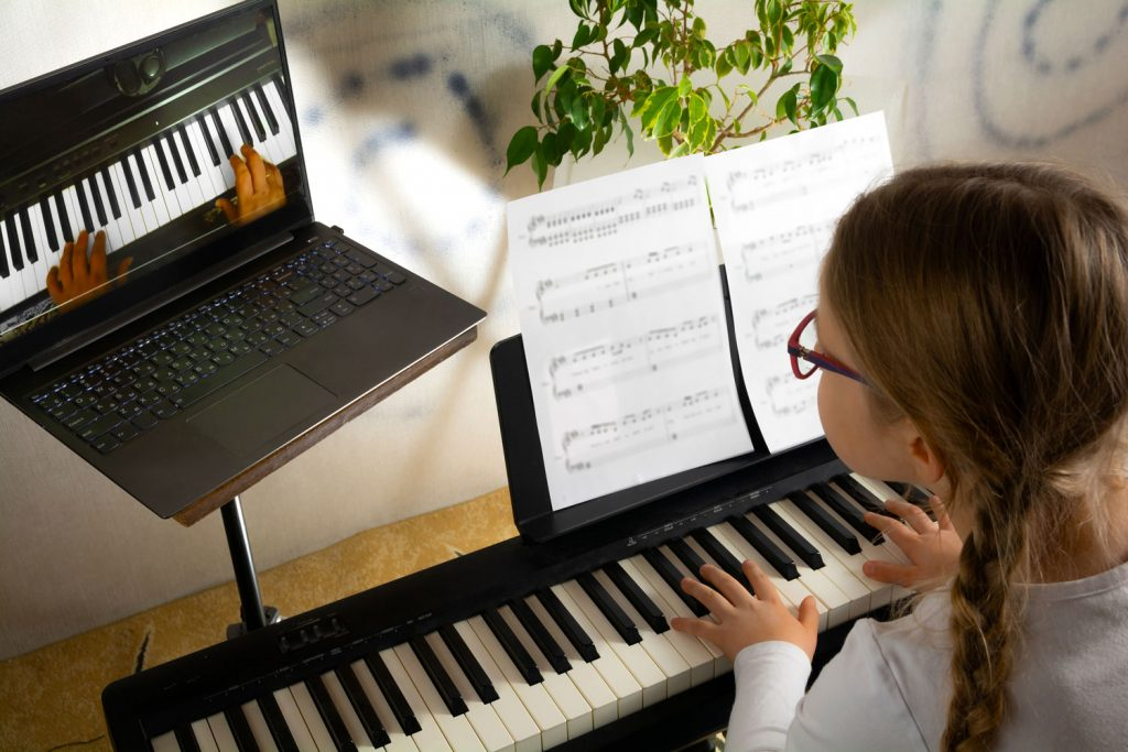 girl learning to play piano via online piano lesson