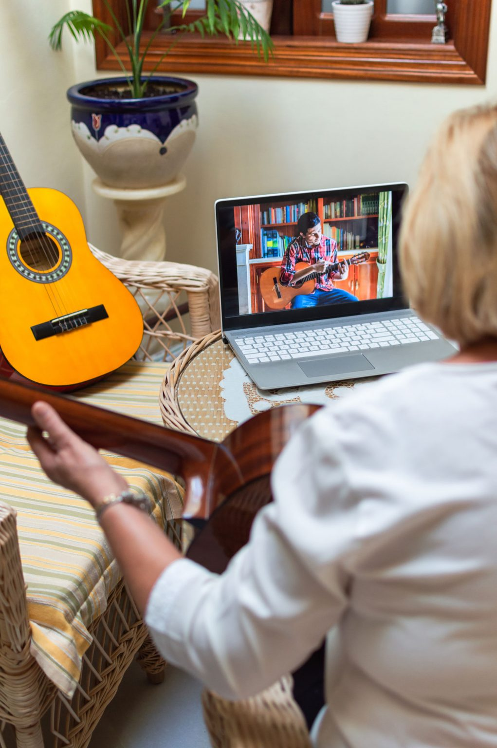 guitar instructor teaching her student online