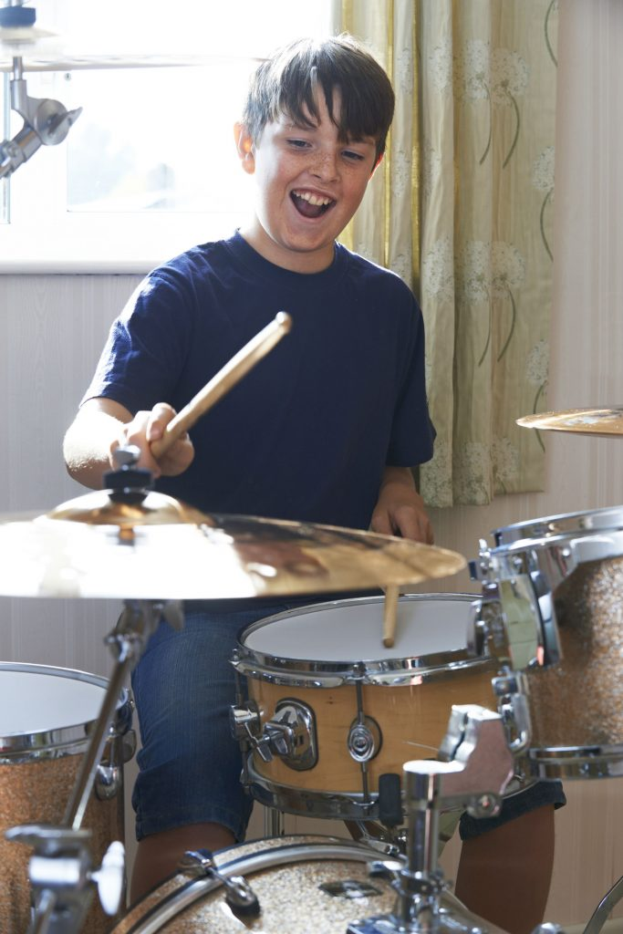 Happy boy playing the drums