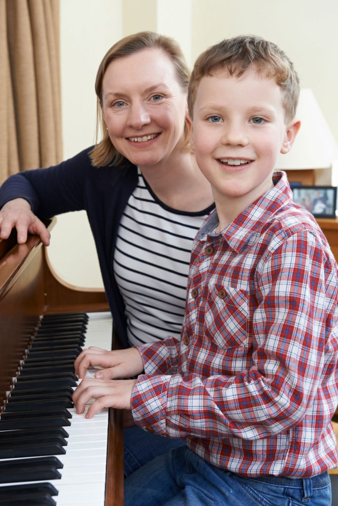 piano instructor with her young boy student