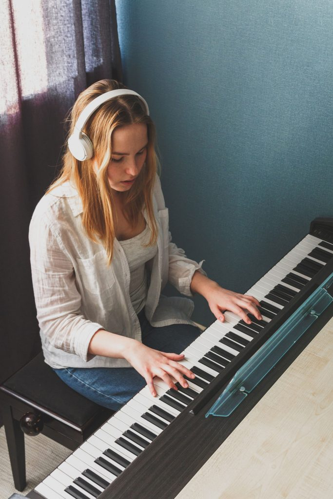 teenage girl playing the piano while wearing headphones