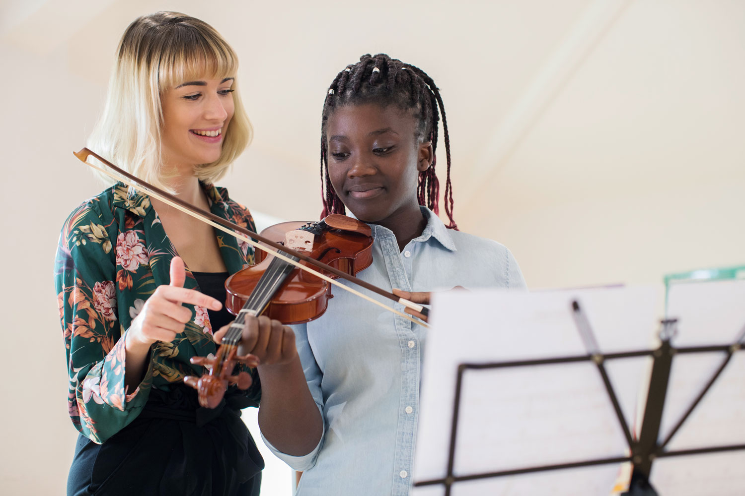violin instructor teaching her young female student