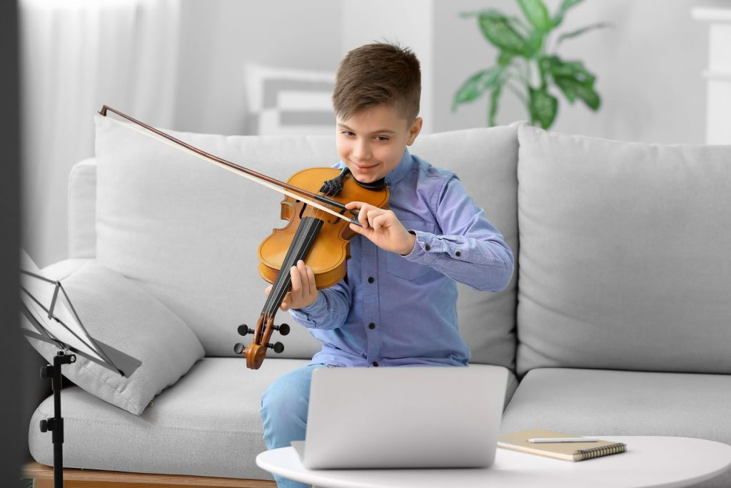young boy having a violin lesson online