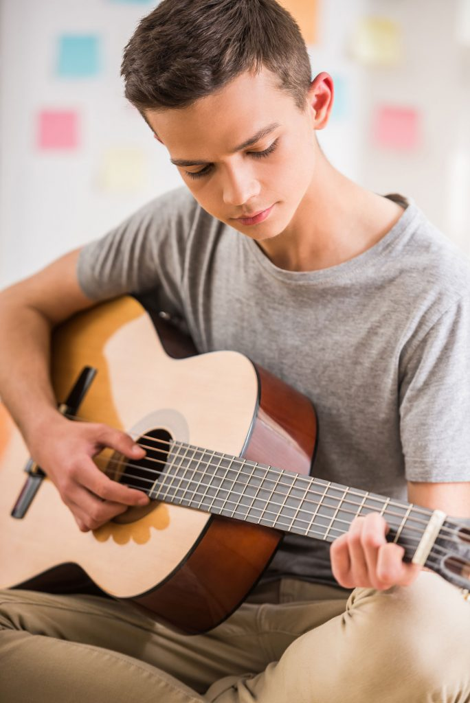 young teen playing the guitar
