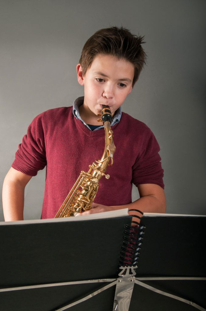 young boy student playing saxophone