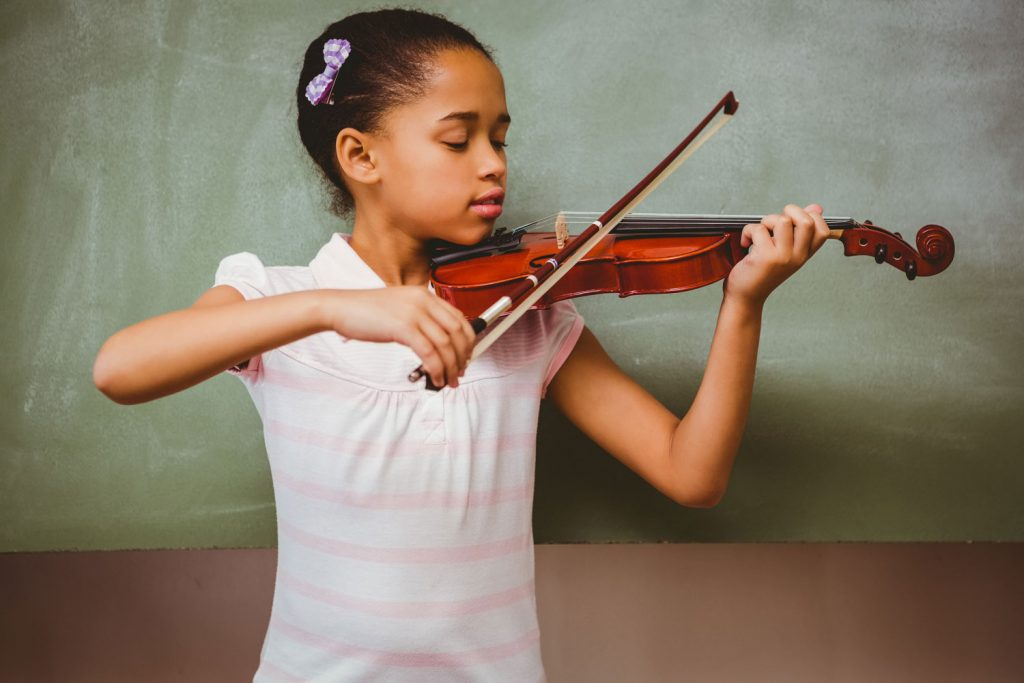 young girl plays the violin while looking at it