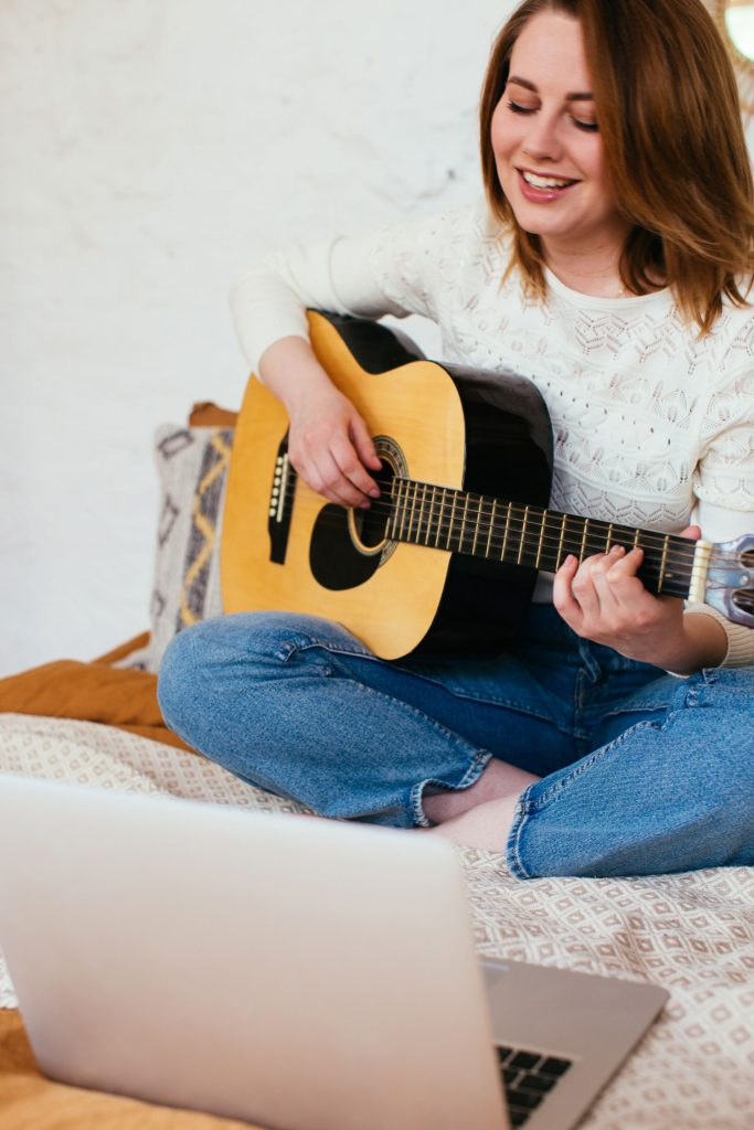 young girl playing guitar and singing