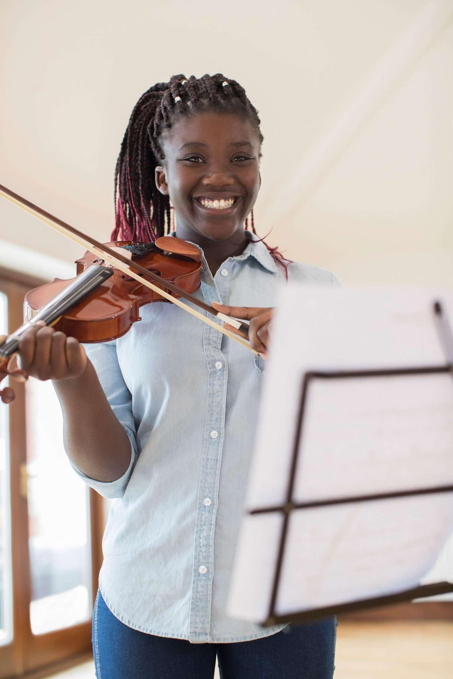 young violin student smiling at the camera