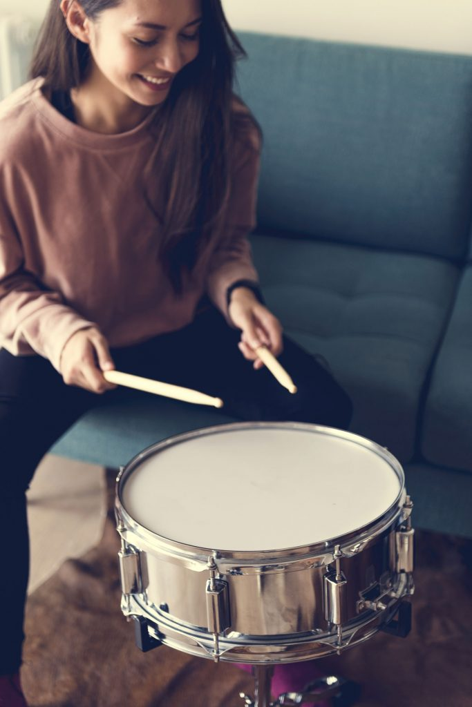 happy young woman playing the drum