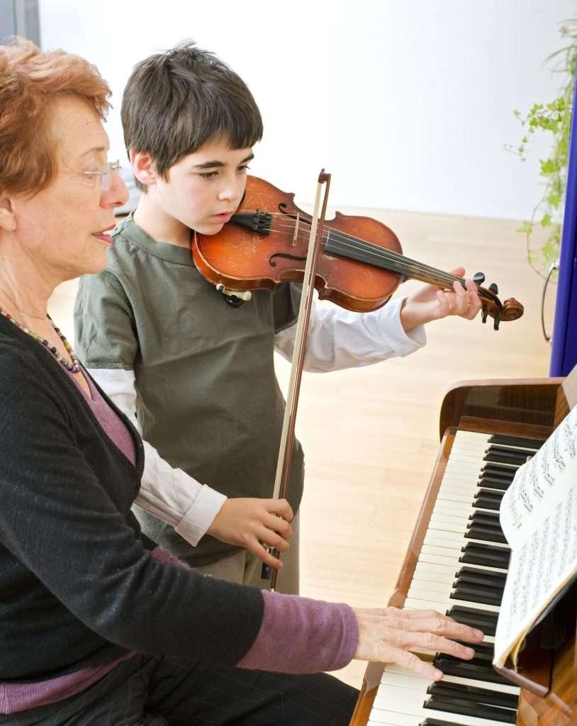little boy having a violin lesson