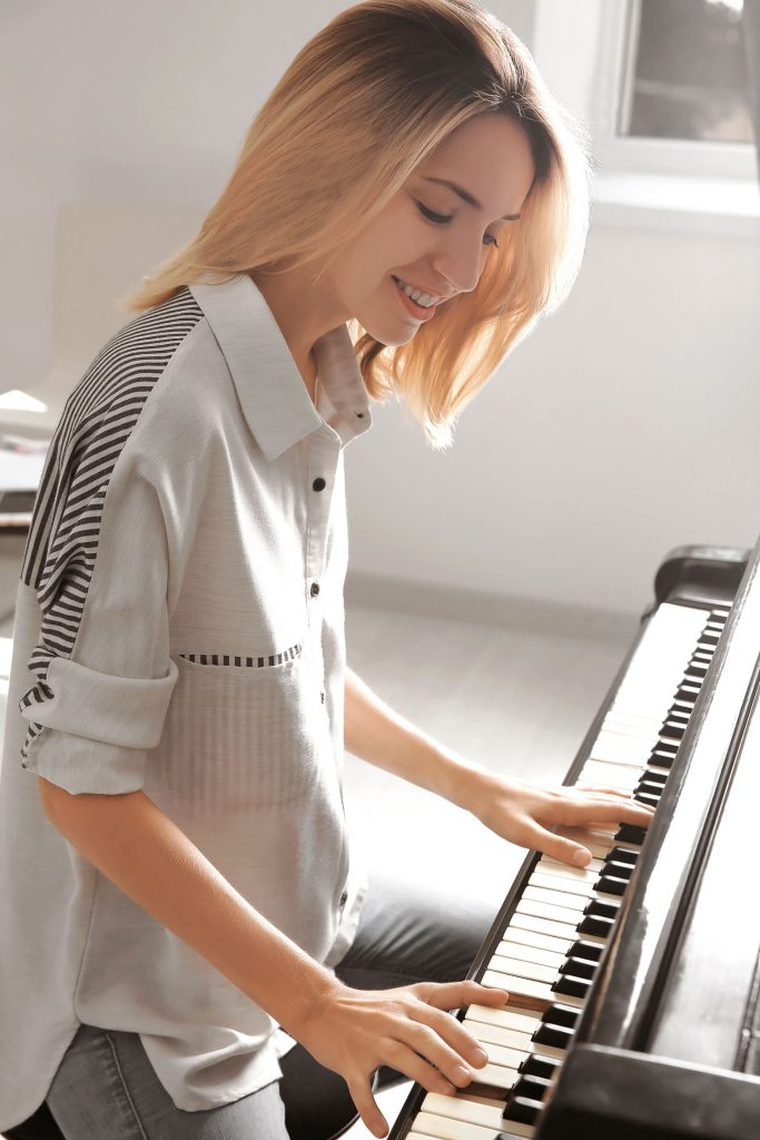 talented young woman playing piano indoors