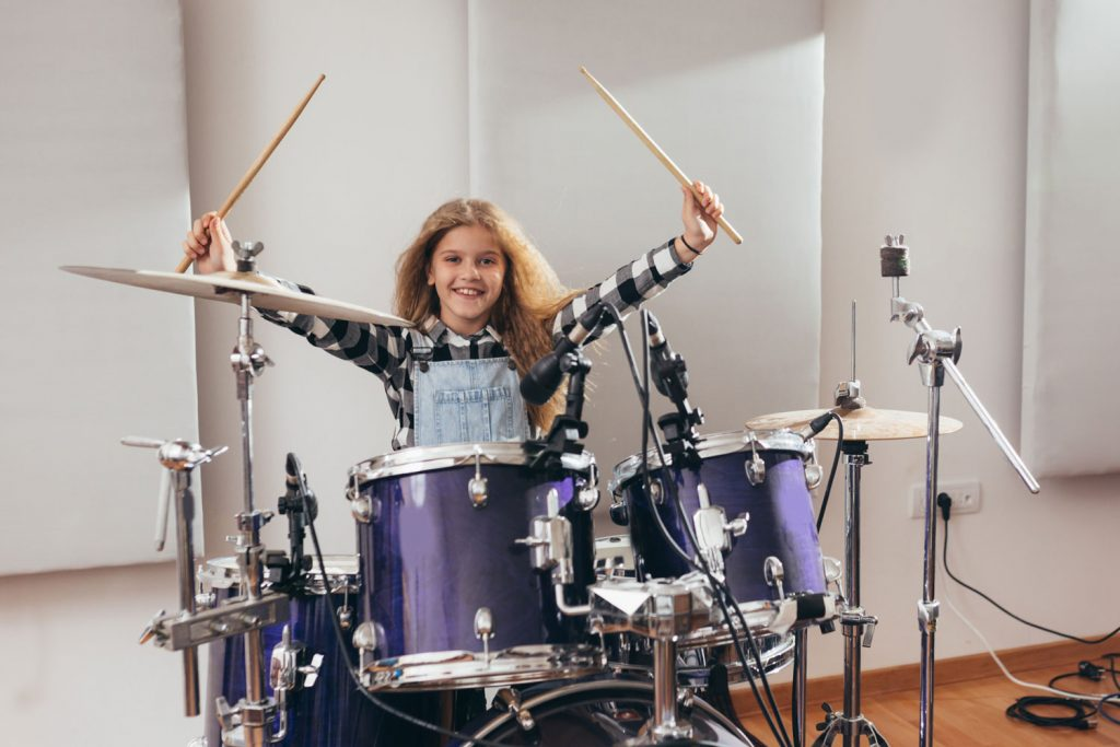 happy young girl playing the drums